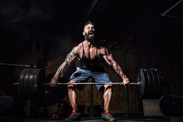 Homme de fitness musclé faisant soulevé de terre d'une barre dans le centre de remise en forme moderne. entraînement fonctionnel.