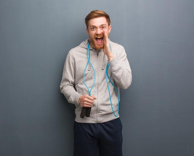 Homme de fitness rousse jeune criant quelque chose de heureux à l'avant. il tient une corde à sauter.