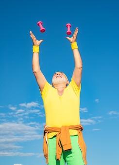 Homme de fitness senior s'entraînant avec des haltères isolés sur fond bleu, l'âge n'est pas une excuse pour se relâcher ...