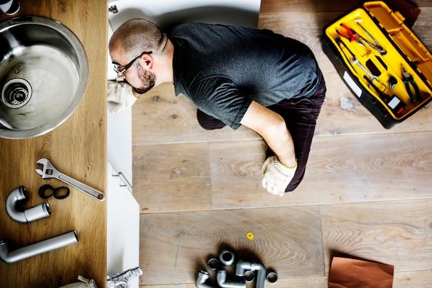Homme fixant un évier de cuisine