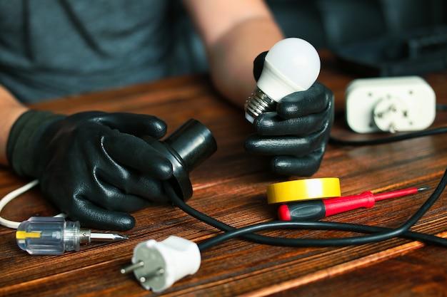 Homme fixant les fils de la lampe de bureau électricien réparant les lumières et le concept de lieu de travail de service