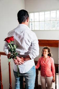 Homme avec des fleurs derrière le dos près de femme heureuse