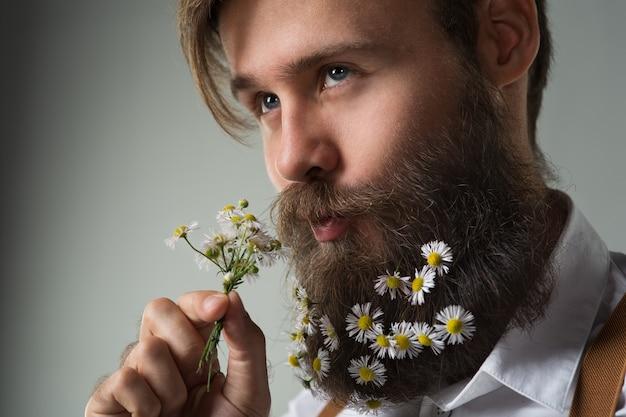 Homme avec des fleurs de marguerite décorée de barbe en chemise blanche et bretelles sur fond gris