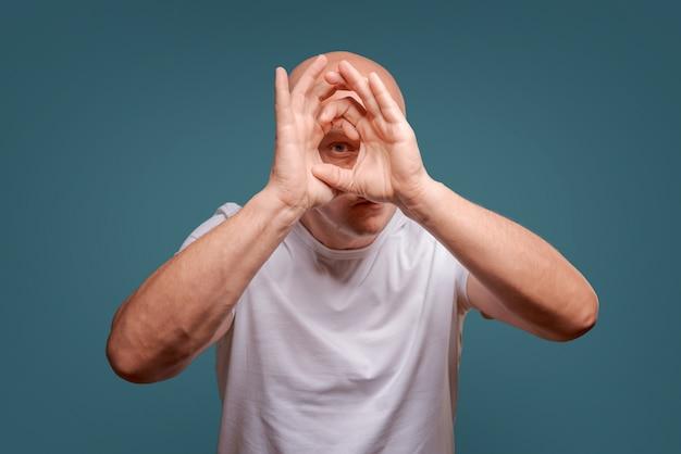 Un homme sur un fond bleu en tenant ses mains près de ses yeux comme un télescope