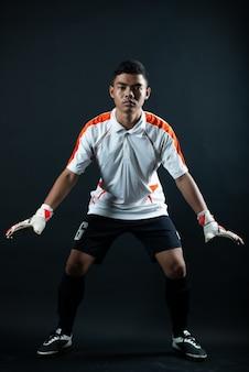 Homme de football jeune gardien isolé de l'équipe de football de l'académie