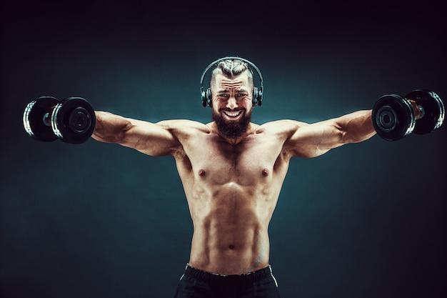 Homme formation de muscles avec des haltères en studio sur fond sombre.