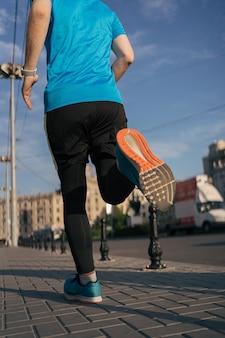 Homme en forme attrayant courir dans la ville
