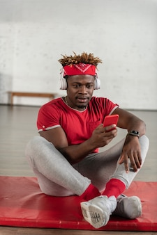 Homme en forme concentré assis sur un tapis sportif avec des écouteurs dessus