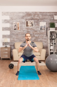 Homme en forme entraînant ses jambes sur un tapis de yoga pendant la pandémie mondiale.
