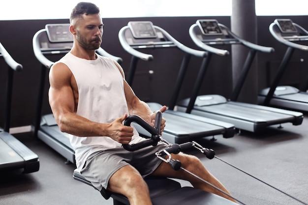 Homme en forme et musclé effectuant des exercices sur le simulateur.