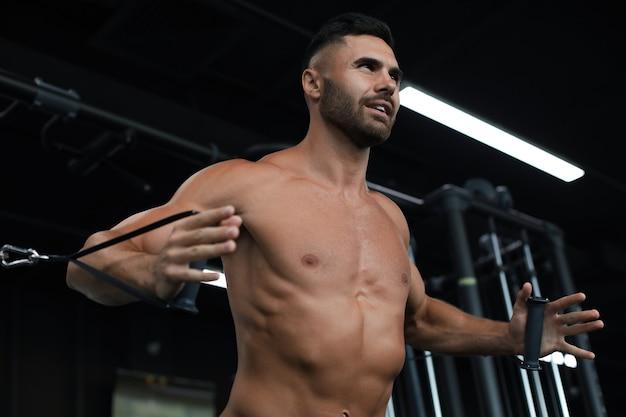 L'homme en forme et musclé entraîne les muscles pectoraux sur un simulateur de bloc dans la salle de gym.