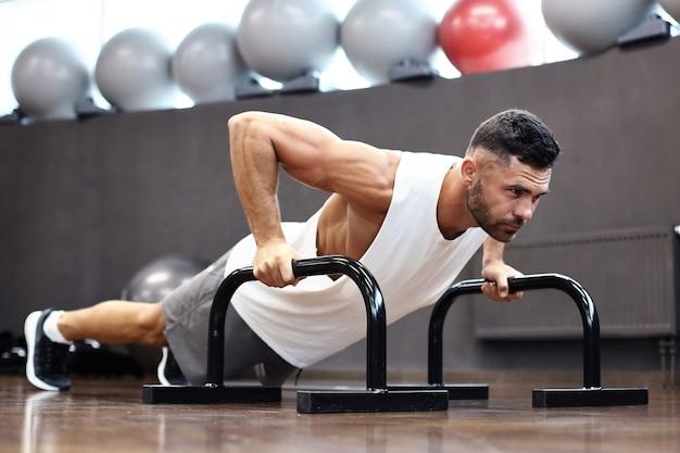 Homme en forme et musclé faisant des pompes horizontales avec des barres dans la salle de sport.