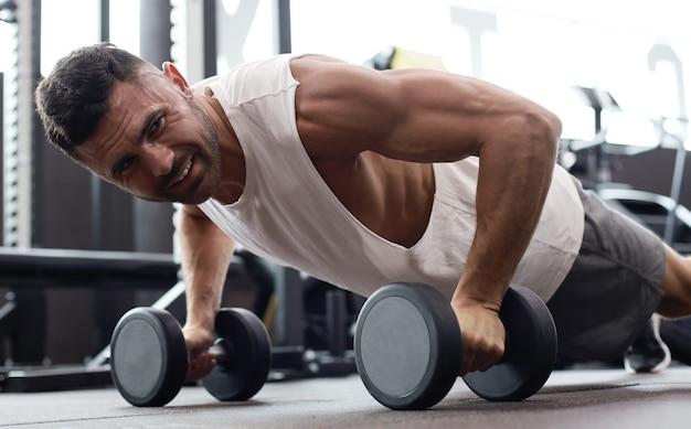 Homme en forme et musclé faisant des pompes horizontales avec des haltères dans une salle de sport.