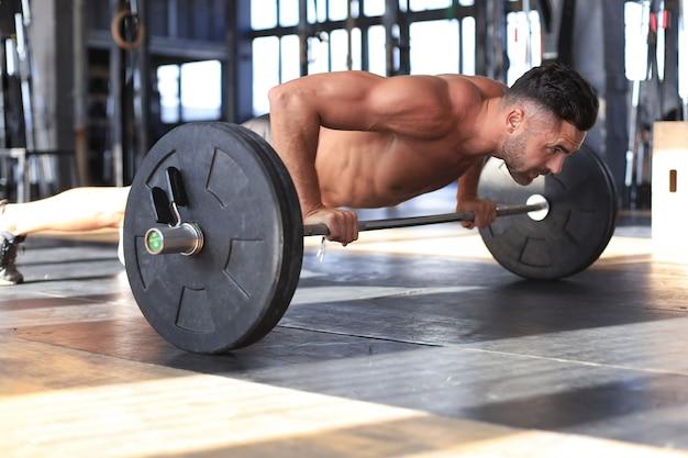 Homme en forme et musclé faisant des pompes horizontales avec haltères dans une salle de sport.