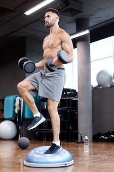 Homme en forme et musclé s'entrainant avec des haltères sur une boule de gymnastique hémisphère bosu dans une salle de sport.