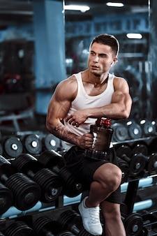 Un homme formé sexuellement boit de la nutrition sportive après un entraînement intense, les mains, les pieds, le dos, les biceps et les triceps