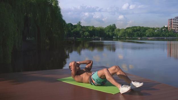 Homme fort actif faisant des exercices d'abs sur la jetée du lac en bois
