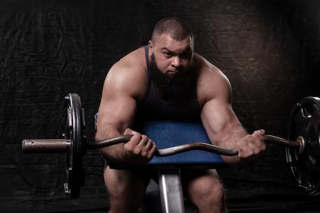 Un homme fort avec une barbe exerçant ses bras sur un banc scott