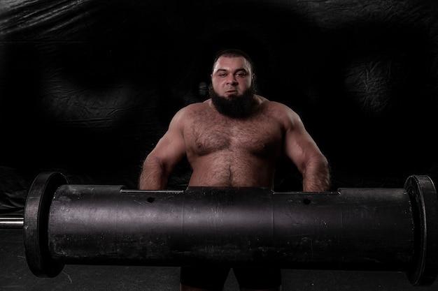 Un homme fort barbu tient une grande bûche de fer dans ses mains