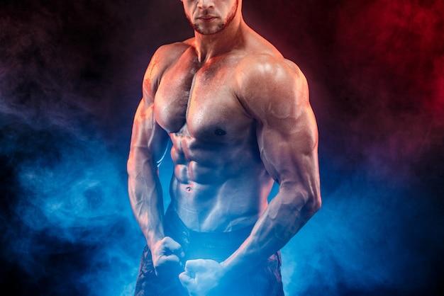 Homme fort bodybuilder en pantalon militaire avec abdos, épaules, biceps, triceps, poitrine parfaits