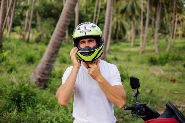 Homme fort sur le champ de la jungle tropicale avec moto rouge