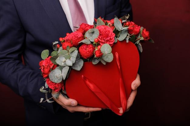 Homme fort en costume tenant dans une main une boîte rouge de roses