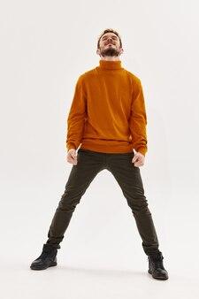 Un homme fort dans un pantalon de chandail orange et des bottes dansant sur un fond clair