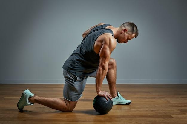 Homme fort, faire de l'exercice avec ballon med. photo d'homme parfait physique sur fond gris. force et motivation.