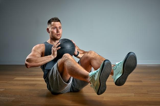 Homme fort, faire de l'exercice avec ballon médical