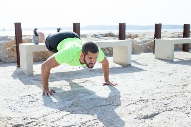 Un homme fort faisant des pieds poussés élevés au bord de la mer