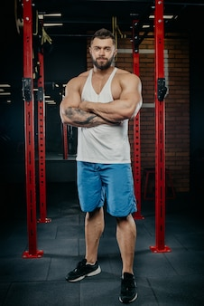 Homme fort musclé avec des tatouages et de la barbe posant dans un débardeur blanc et un short bleu dans la salle de gym.