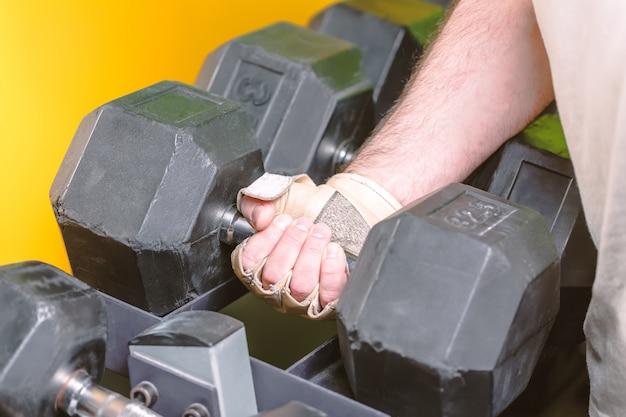 Homme fort prenant un haltère noir de rack dans un centre de fitness sport.