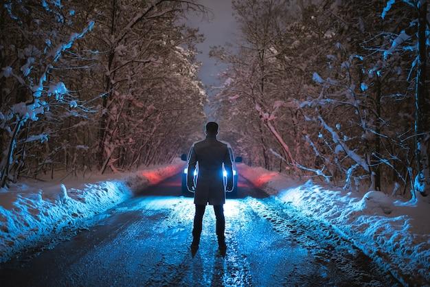 L'homme fort se tient près de la voiture sur la route enneigée. le soir la nuit