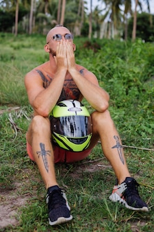 Homme fort tatoué sur champ de jungle tropicale avec moto rouge