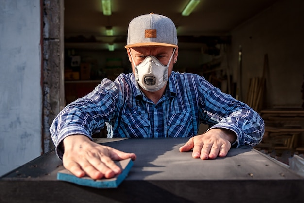 Un homme fort en vêtements de travail travaille dur et se lave, polit un chiffon avec une table noire en bois