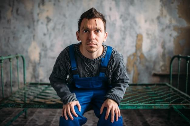 Homme fou assis sur un lit rouillé, paupières ouvertes scellées avec du plâtre, patient psychopathe déprimé. concept de personnes malades mentales, humain fou