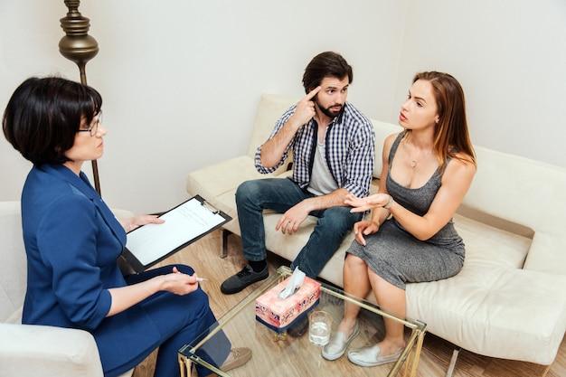 Un homme fou est assis avec sa femme sur le canapé et la regarde. il pointe sa tête, ce qui signifie qu'elle est folle. fille parle au thérapeute