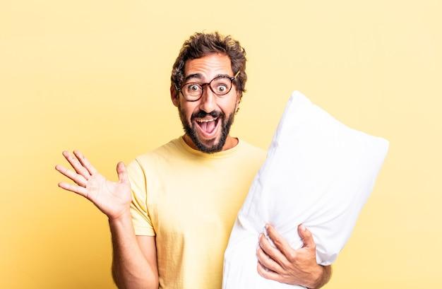 Homme fou expressif se sentant heureux et étonné de quelque chose d'incroyable et tenant un oreiller