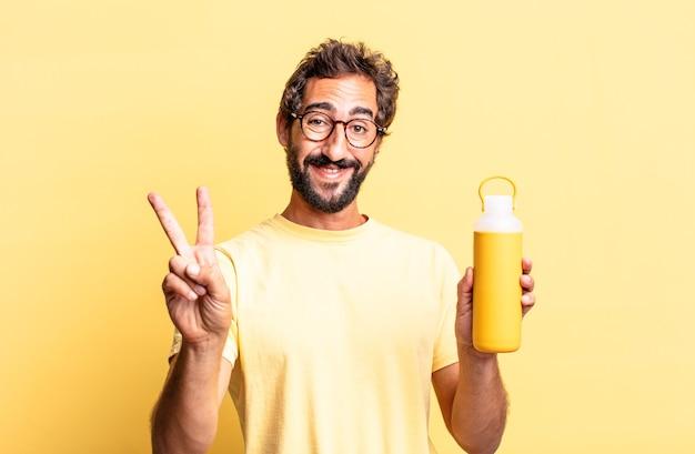Homme fou expressif souriant et ayant l'air heureux, gesticulant la victoire ou la paix avec un thermos à thé