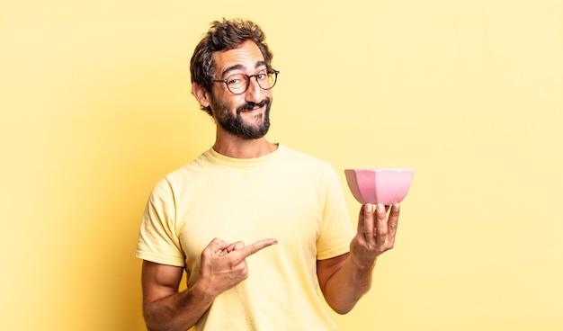 Homme fou expressif souriant gaiement, se sentant heureux et pointant sur le côté et tenant un pot