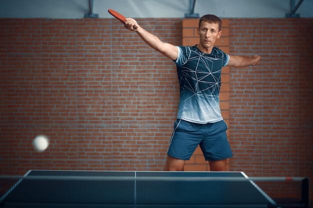L'homme frappe la balle en jouant au tennis de table