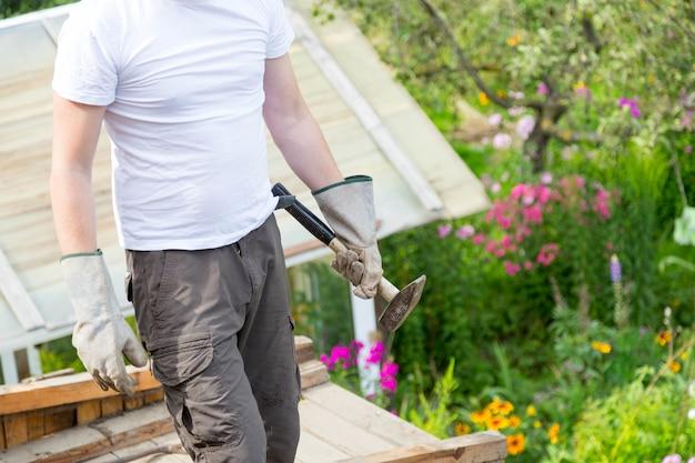 L'homme frappe une vieille planche de bois pourrie avec un marteau de l'analyse du toit