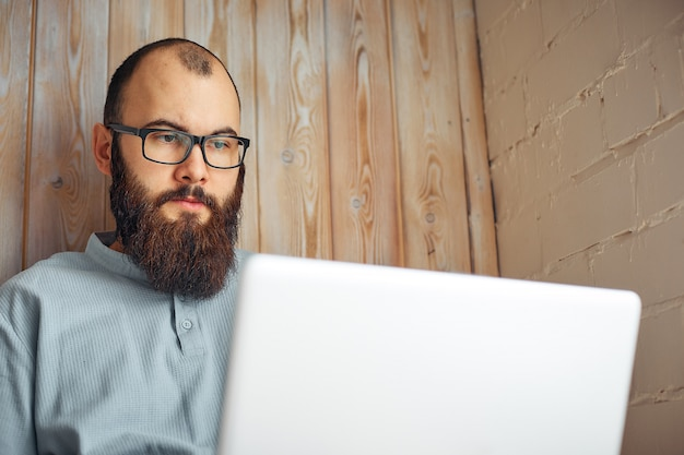 Homme de freelancer réussi avec barbe de style de vie atteint un nouvel objectif avec un ordinateur portable à l'intérieur du loft