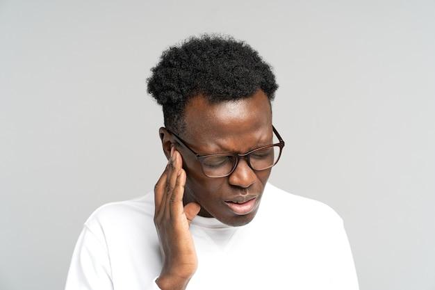 Homme fronçant les sourcils souffrant d'acouphènes mal d'oreille palpitant fatigué du bruit touchant l'oreille douloureuse