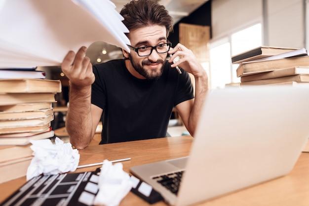 Homme frustré par les notes sur l'ordinateur portable assis au bureau.