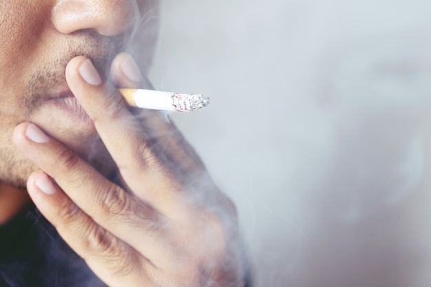 Homme fumant une cigarette. la fumée de cigarette se propage.