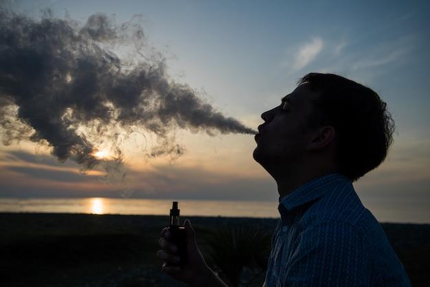 Homme fumant vaping e-cigarette vape box mode over golden sunset