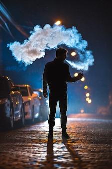 L'homme fume une cigarette électrique dans la rue. le soir la nuit