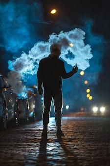 L'homme fume une cigarette électronique à l'extérieur. le soir la nuit
