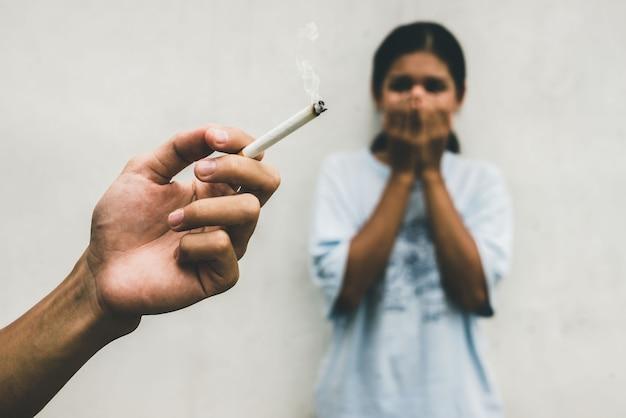 L'homme fume la cigarette et la femme se couvre le visage. le tabagisme passif et les soins de santé ou le concept de journée sans tabac.